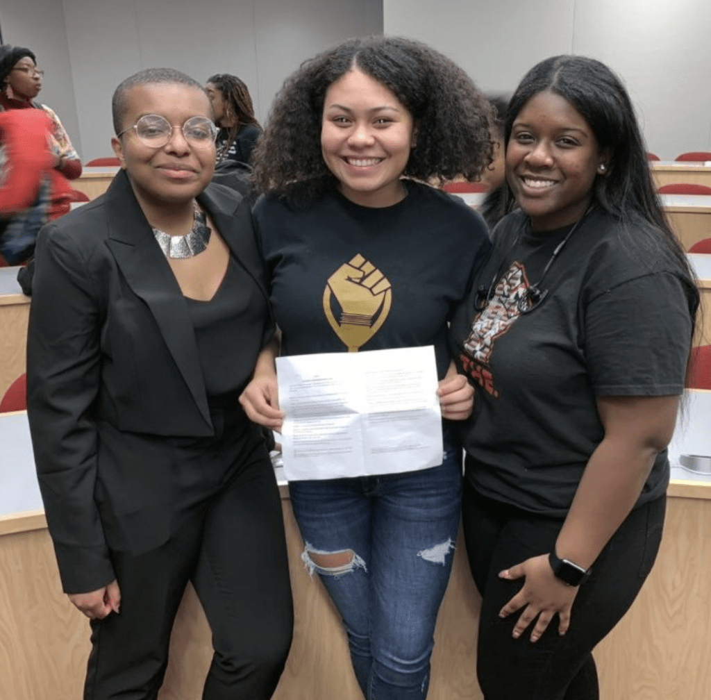 Ose Arheghan, Destiny Brown and Amanya Paige holding passed resolution to add Black Caucus to USG.