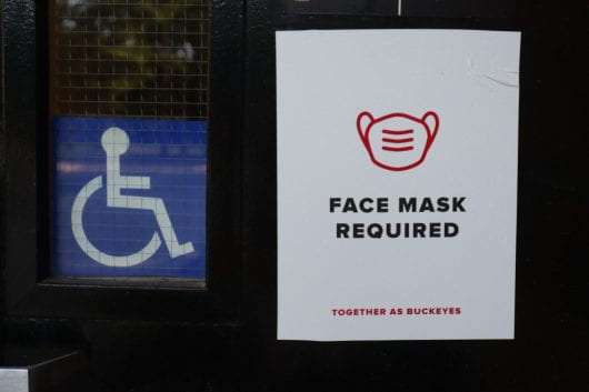 """sign on door of building that with image of mask and """"face mask required"""" next to a wheelchair sign"""