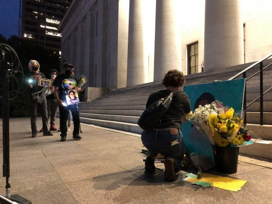 woman kneels in front of Breonna Taylor painting at Ohio Statehouse