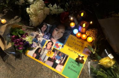 Candles and flowers are placed around pictures of Breonna Taylor