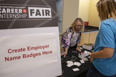 An Ohio State students reaches to make an employer name badge while at the 2019 Ohio State career fair
