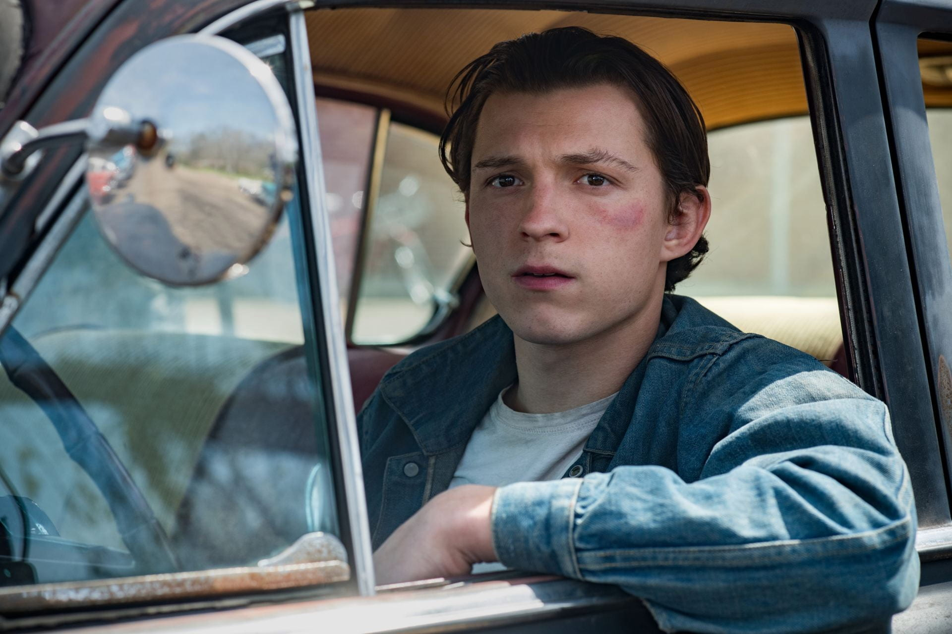 Tom Holland driving a car and looking out the window