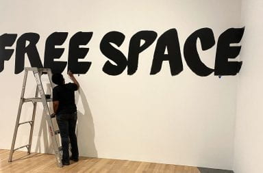 "A person paints in black letters ""free space"" on a white wall"