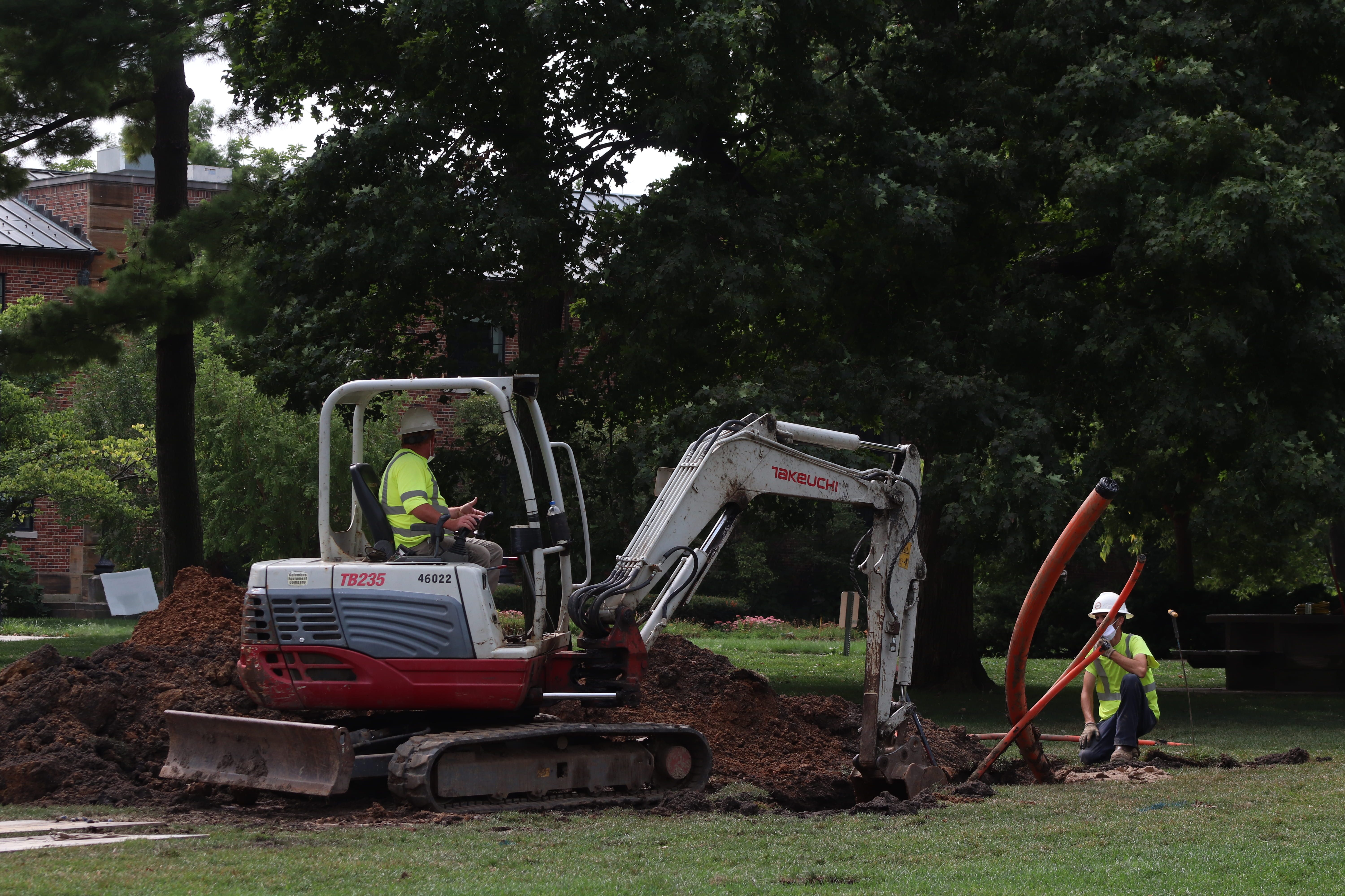 man drives construction vehicle digging hole in Oval
