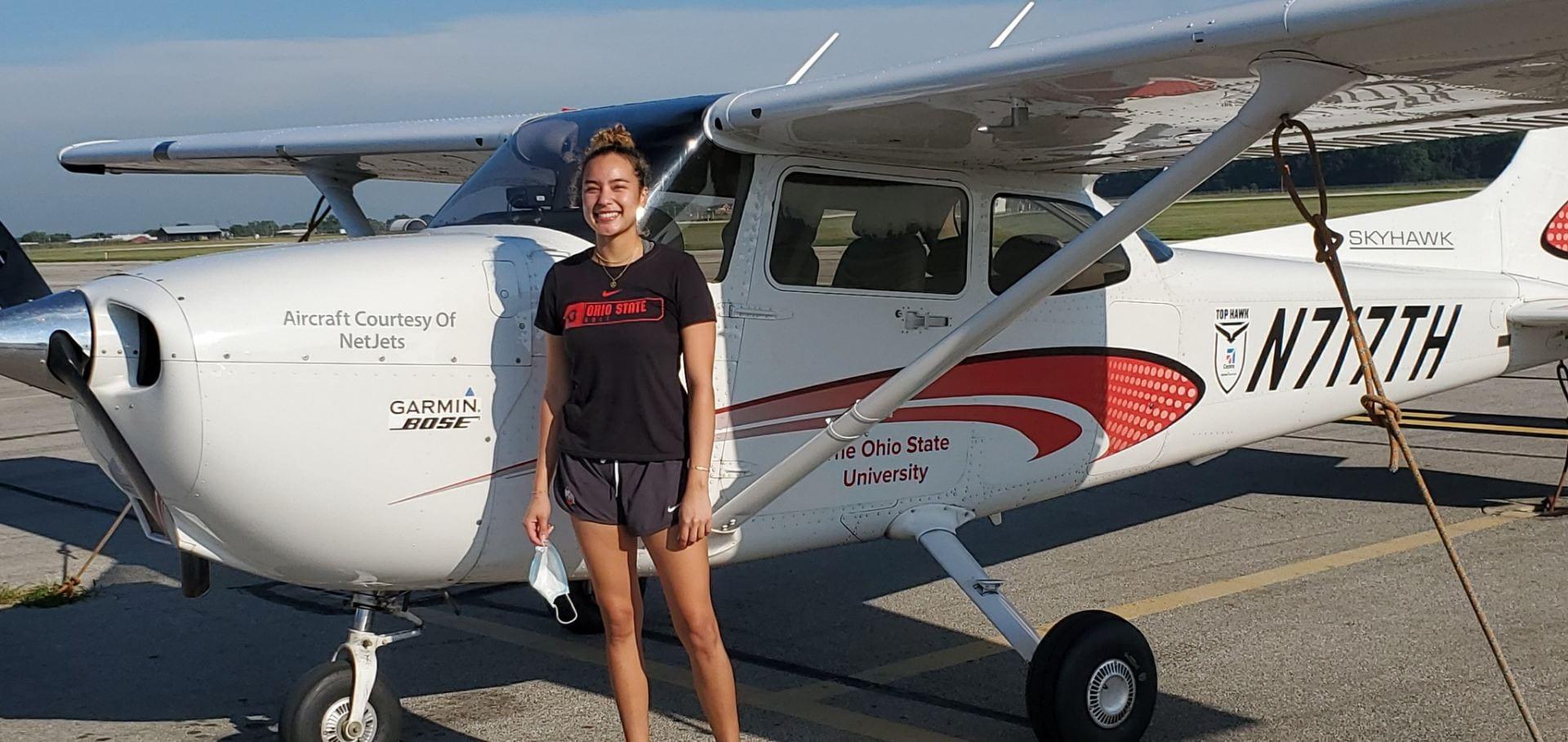Alanis Sakuma stands next to a small aircraft