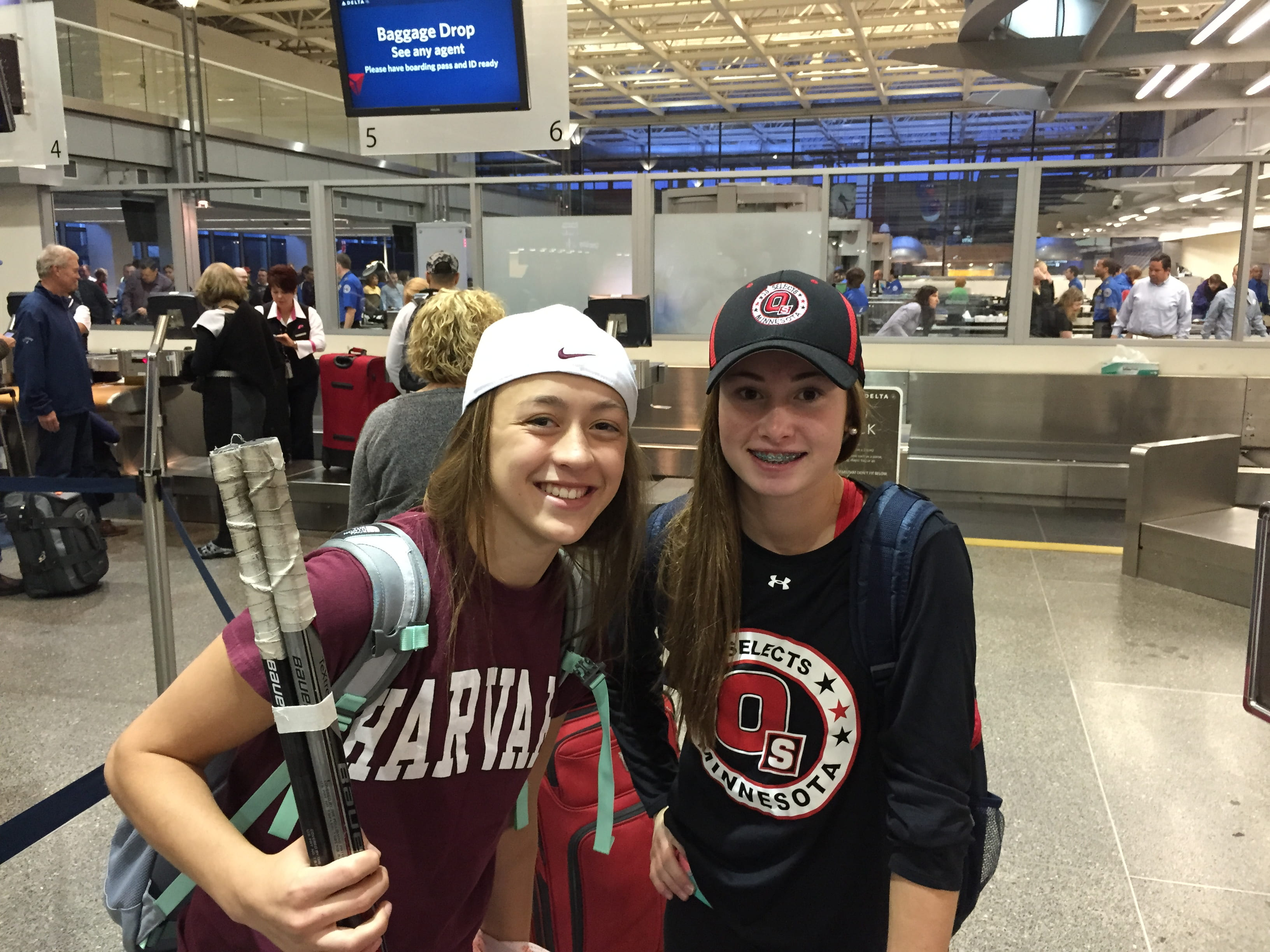 Ramsey Parent and Gabby Rosenthal pose together inside an airport in hockey attire