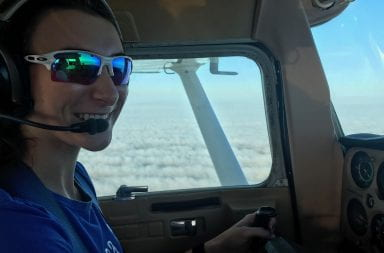 Jillian Bourdage sits in the pilot seat as she flies