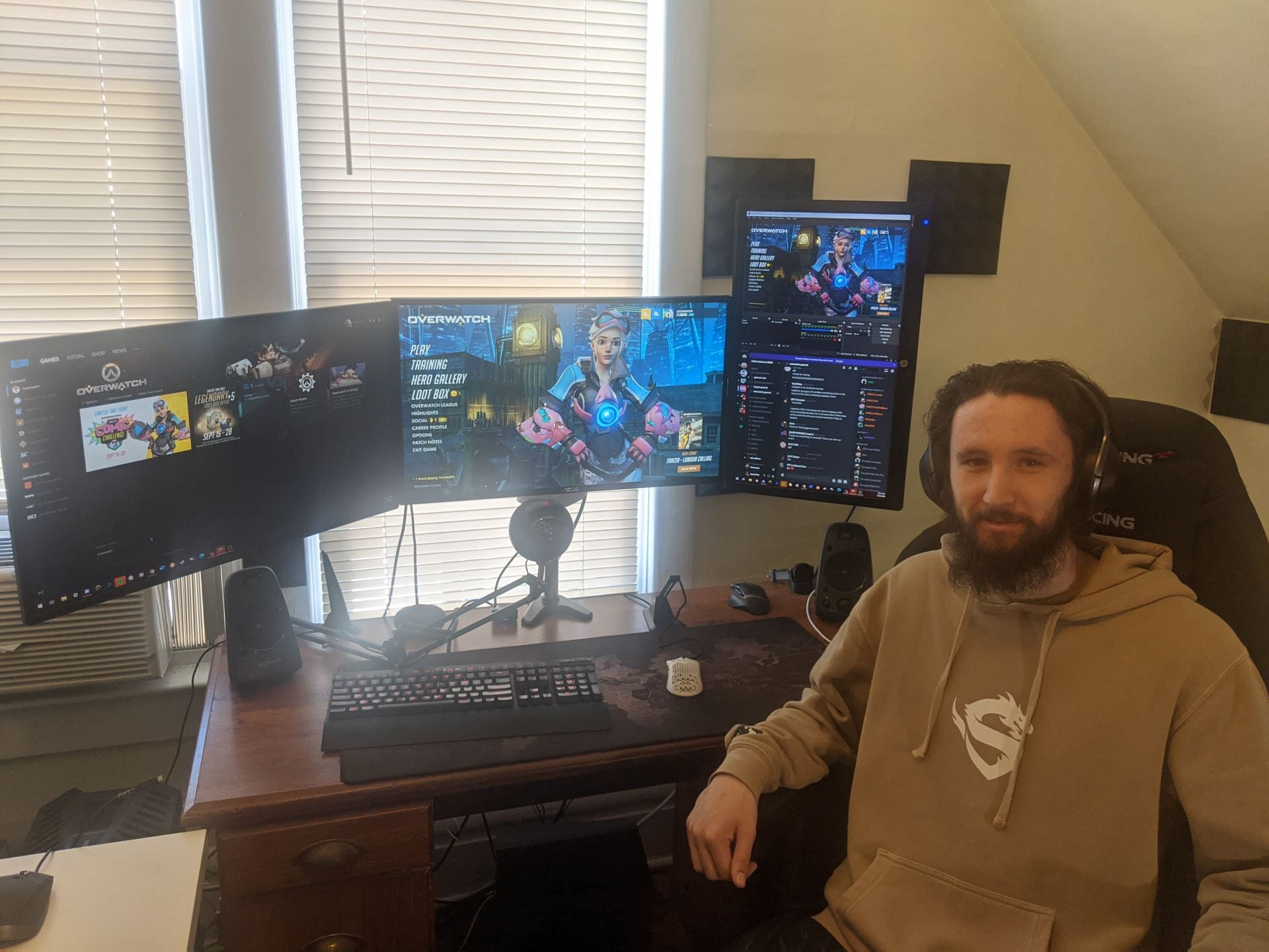 Jake Blitch sits in front of his computer set up with three monitors