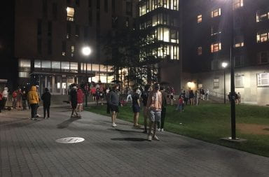 Students stand outside of a south campus dorm after being evacuated due to the smell of natural gas after midnight