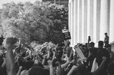 a photo of protesters in columbus following george floyds death. protestors hold signs and their fists up in the air