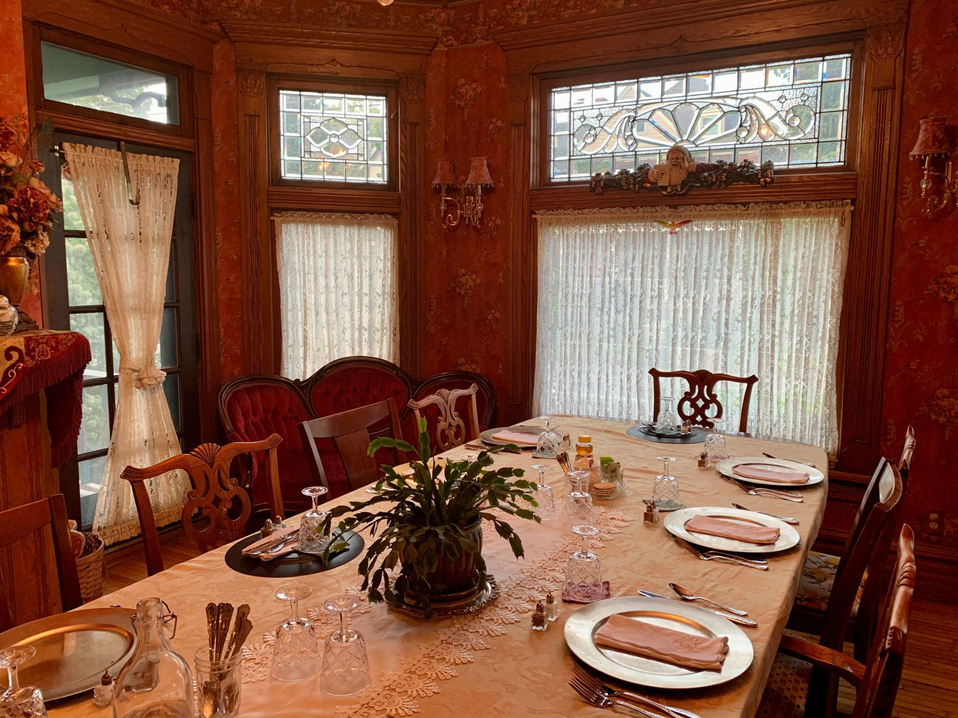 a dining room sits empty with the place setting all in place inside the harrison house bed and breakfast