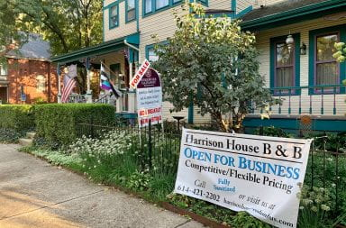 the outside of the harrison house bed and breakfast with a for sale sign along with an open for business sign in the front yard