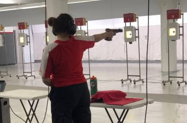 Emily aims her pistol at the target