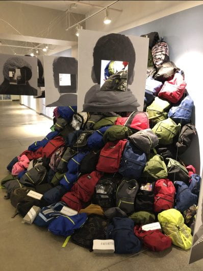 a mound of backpacks stacked on top of eachother against a wall