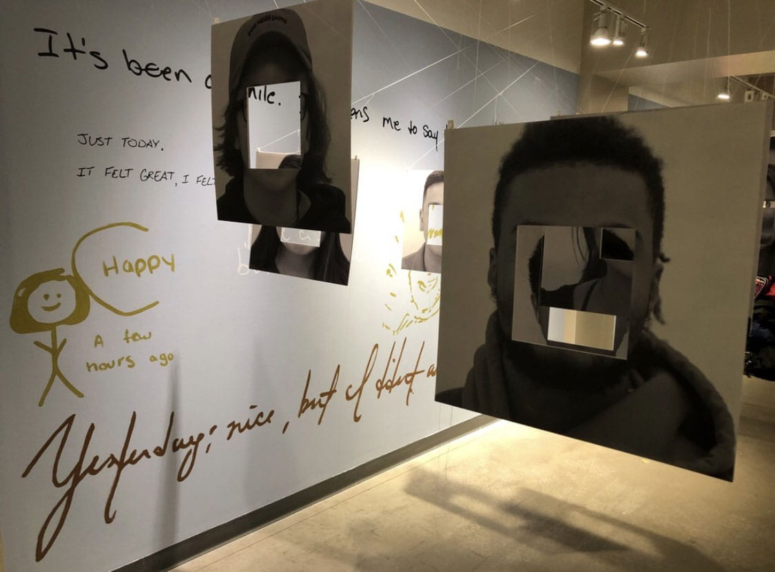 photographs with the faces cut out are hanging on a glass wall where you can look through the hole cut out