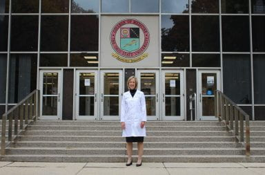 Carol Bradford stands infront of the college of medicine