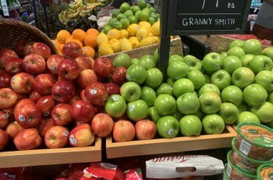 red and green apples line the table at the grocery store in the produce section