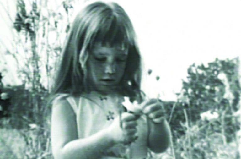 a little girl holding daisys in the field