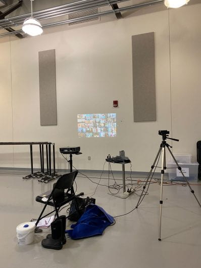A classroom set up with a projector and miscellaneous AV and dance equipment