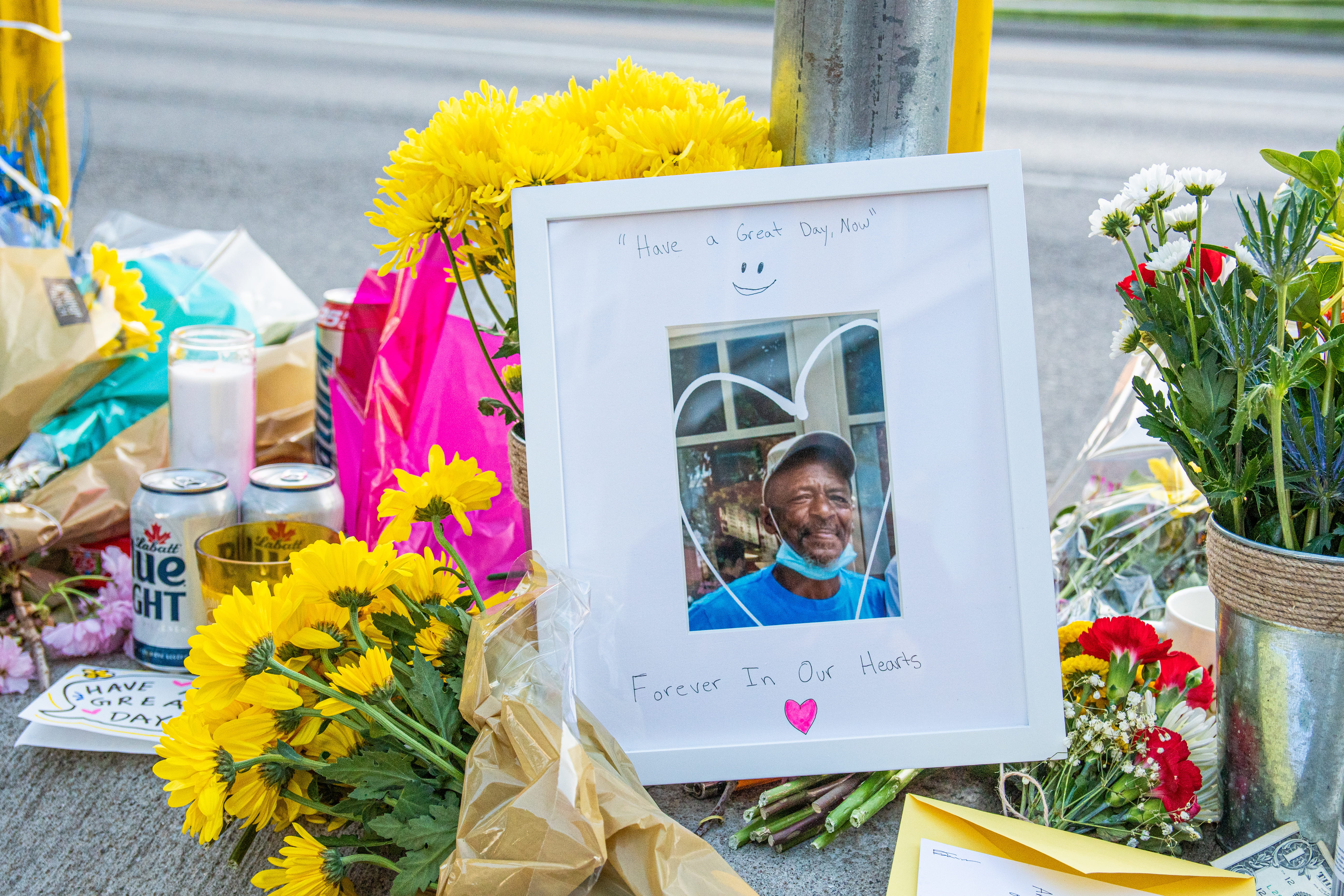 A framed picture of a Black Man sits among flowers and candles