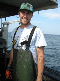John Holden aboard a lobster boat in Long Island Sound, bespattered with mud but still smiling.