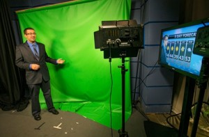 Michael Colbert uses the School of Journalism's green screen for a weather forecast