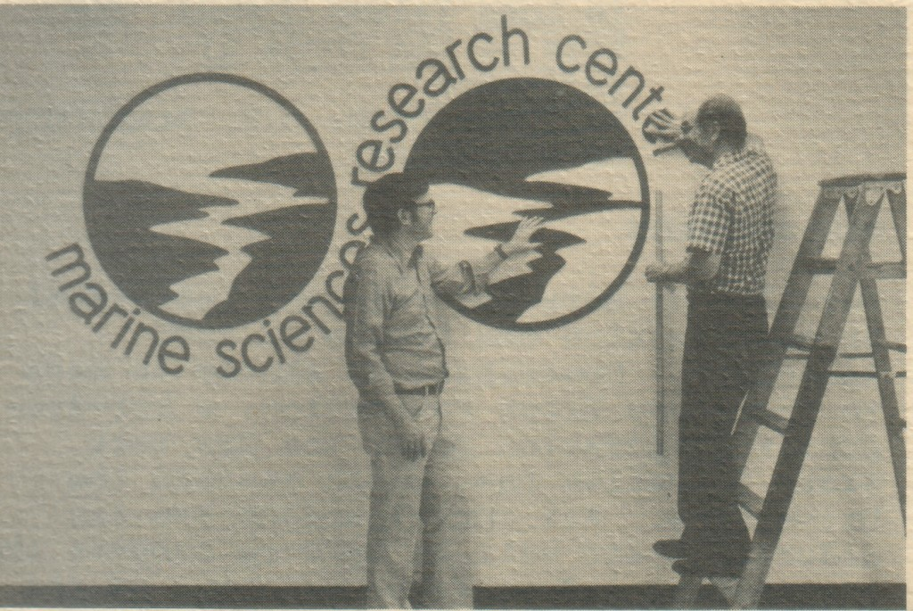 MSRC's logo is  prominently displayed in Endeavour Hall. Former director J. R. Schubel, left, enlisted the services of his father-in-law, Dr. Marion Hostetler, Montpelier, Ohio, in the execution of the design. The logo consists of reduplicated circles depicting an estuary emptying into the ocean. The circle on the left is green, representing land and vegetation, while the one on the right is blue, representing the estuary and the sea. The logo graphically depicts MSRC's commitment to the coastal environment.