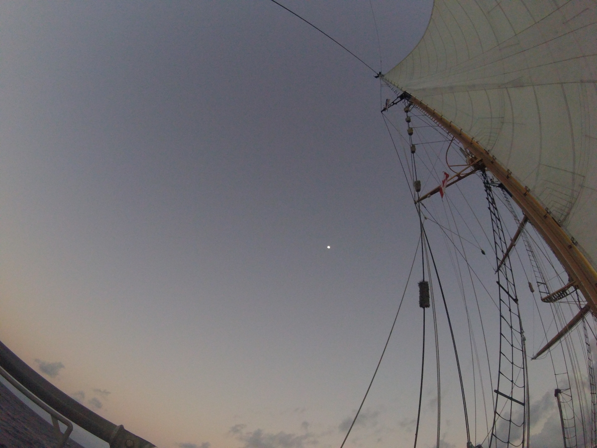 From the quarterdeck under the main sail at dusk, with the moon off the portside.